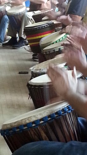 people playing djembe drums in class